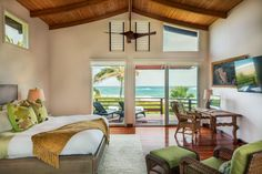 This island-themed bedroom leans on a neutral palette paired with vibrant green accents to create a lively room design. An exposed beam vaulted ceiling and cherry hardwood floors add an exotic touch, while floral throw pillows keep the decor fun. Sliding glass doors provide access to the deck with a waterfront view.
