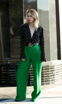 Courtney Trop of Always Judging wears a printed plunging v-neck blouse, high-waisted green trousers, boots, and a Gucci belt