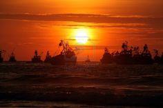 Las olas, barcos de pesca y puesta de sol en el mar en Máncora, Perú.