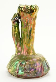"""Delphin Massier (French, 1836-1907) A Vase. Iridescent glazed figural ceramic vase depicts a maiden resting her head on the side of a tree. Bulbous lower portion of vase is decorated with butterflies. Underside is signed """"Delphin Massier Vallauris A.M."""". Additionally incised """"Delphin Massier"""" in the opposite direction of the other signature Height: 12"""""""