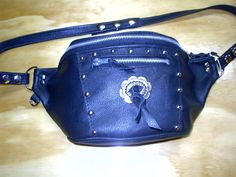 Black leather waist pouch. Zip top closure and outside pockets. Adjustable snap belt. Reg $68.00, SALE $48.00