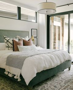 Soft green hues with a splash of pink and black is a surprisingly fresh combination for a bedroom