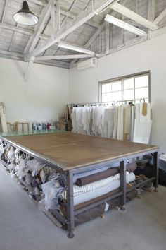 A workroom with a pattern-cutting table and rolls of fabric.