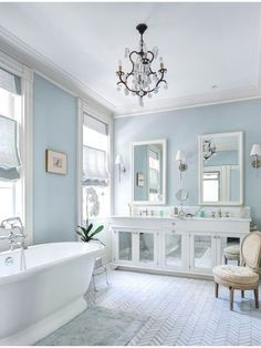 A white bathroom with pale blue walls, a mirrored vanity, and a herringbone tile floor pattern. Source: www.zillow.com/...