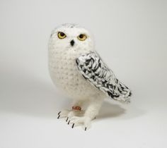 "A life-like Snowy Owl hand-crocheted from soft, brushed alpaca, mohair and  silk, with pure carded British Shetland lambswool filling and needle-felted  detailing around his eyes and face. His wool-wrapped wire feet and claws  are gently poseable and he is signed with a uniquely numbered metal ring on  his leg.   He is just under half life-size, standing 23 cm high by 21 cm from head to  tail (about 9"" x 8"").  I hand make each Snowy Owl to order which takes 1-2 weeks. Though your owl  will…"