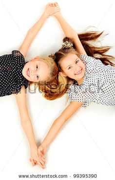 Portrait of two little girls sisters posing at studio. Isolated over white. by Kiselev Andrey Valerevich, via ShutterStock