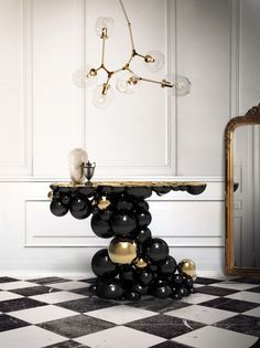 Newton Console -  This intriguing console is ideal for any modern living rooms, bedrooms and hotel lobbies characterised by luxury interior design furnishings. This monumental console made from aluminium and lacquered in black, with a high gloss varnish. The spheres and semi spheres that complete this futuristic console are gold plated.