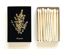 Light a summer spark with this pretty herb matchbox! Adorned with a miniature botanical illustration of a thyme sprig on the outer lid in your choice of foil press color, this tiny matchbox adds the perfect botanical touch.  Great for collecting, giving, having on the table at