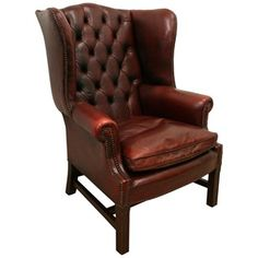 Late 20th century, Georgian style burgundy leather wing chair, with the classic deep buttoned back and shaped wings. The leather is held in place by close brass studding which continues around the entire frame.