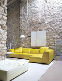 Yellow leather sofa cushion rough stone walls, white table