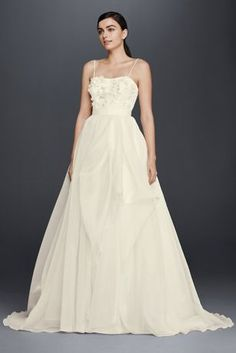 This lightweight organza wedding dress takes a flirty approach to the figure-flattering A-line silhouette. The beautiful bodice is designed with a sweetheart neckline, spaghetti straps, and fun 3D floral appliques.  CheersCynthia Rowley, exclusively at David's Bridal  Sweep train  Back zipper; fully lined  Dry Clean  Imported  Also available in Plus Size, Extra Length and Plus Size Extra Length Protect your dress for years to come with our Wedding Gown Preservation Kit.
