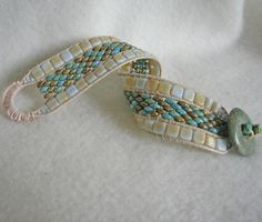 This bracelet is adapted from Deb Roberti's pattern, tila and super duo band.  I used Czechmates instead of tilas and stitched it as a triple row leather bracelet instead of using seed bead picots at the end of each row.