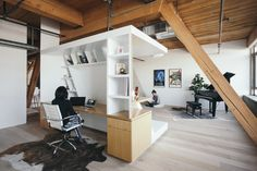 """The Writer's Block is a piece of custom oak veneer millwork that both divides the space and acts as furniture. """"It can be used as a place to lounge, or as a place to retreat and write, or as a place to entertain, and sometimes as a place to just sit and meditate,"""" says design principal Chinmaya Misra of the flexible piece."""