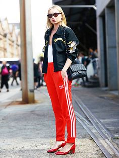 Alexandra Spencer of 4th and Bleeker in red Adidas track pants, black jacket, red heels, sunglasses and black purse