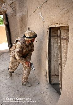 A soldier from 3 Scots, the Black Watch cautiously approaches a room in a compound, whilst searching for narcotics and illegal weapons.