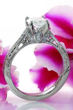 A vintage inspired diamond beauty! Hand engraving and milgrain texture adorn the sides of this antique engagement ring.