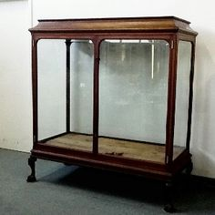 """Beautiful, turn of the century, walnut and beveled glass store display case with carved, claw and ball feet. Measures 5'9"""" tall x 5'4"""" wide x 30"""" deep. Gorgeous! A great deal at 2,000.00, at the Brass Armadillo Antique Mall (816) 847-5260"""