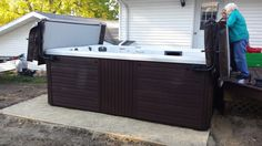 Here is a Master Spas H2X Swim Spa installed on a pea gravel patio next to a deck.