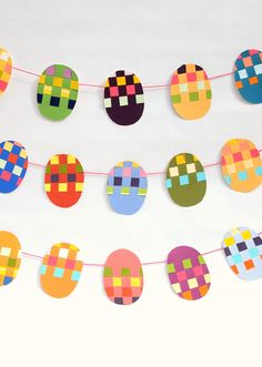 """Woven Paint Chip Easter Banner: Skip the typical """"Happy Easter"""" banner for several string egg banners that are made out of paint chip samples. Click through for more Easter party ideas and decorations that your kids and family will love. Easter Art, Easter Crafts, Easter Bunny, Easter Eggs, Easter Ideas, Kid Crafts, Preschool Crafts, Spring Crafts, Holiday Crafts"""