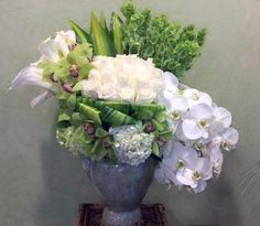 ** This elegant arrangement is in a french style urn and it has only white and green blooms. It has cascading Phalaenopsis orchids, Roses, Hydrangeas, Calla Lilies, Cymbidiums orchid blooms and green Bells of Ireland. $200.00