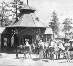1882-1885. Exterior view of the Ute Iron Spring Chateau, Manitou Springs (El Paso County), Colorado. The frame octagonal pavilion has latticework and projecting bays with a shingled, faceted conical roof with ornamental dormer, vent-cap top and flagpole. The 'burro brigade' stands in the sun, numerous girls in wide-brimmed, ribboned hats and frilly dresses, they sit sidesaddle on burrros ready...     Courtesy: Western History/Genealogy Department, Denver Public Library, Denver, Colorado…