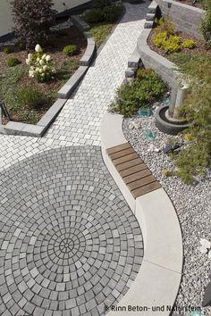 Ciotto® Pflaster im Kreis verlegt mit Sitzbankradienteilen als Einfassung. Hier gibt es Sitzmöglichkeiten und die Kombination verschiedener Grautöne mit der natürlichen Bepflanzung erzeugt eine schöne Außenanlagengestaltung.