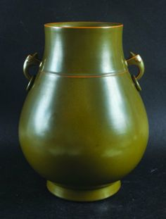 A CHINESE TEA DUST PORCELAIN HU VASE, with moulded animal-head and ring handles, the base with a Qianlong seal mark, 11.75in high.