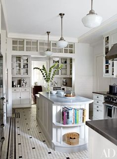 I love the simplicity and thoughtful detail of this kitchen, from the exposed shelving on the island to the splash of windows above the second area of the kitchen. A functional and chic enclosed space. Via AD