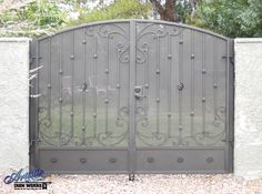 Arched wrought iron double gate with scrolls, knuckles, birds nest and kick plate with rosettes.