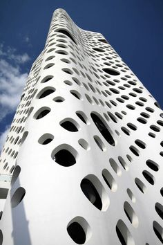 A unique tower that defies conventional high-rise design strategies. A second skin wraps the building, adding an enigmatic depth to the facade, as if the tower were a porous white monolith landed in the landscape.