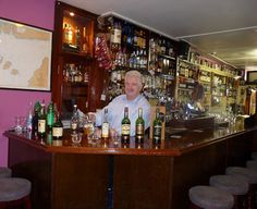 Tony Freeney behind the bar, with some of his Irish whiskeys. At Freeney's Pub & Off