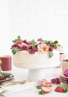 Pink Velvet Cake topped with strawberries, raspberries, pomegranate seeds and edible flowers.