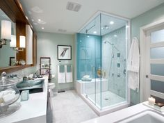 Candice wanted to give the owners of this bathroom a place to unwind after long, stressful days. A watery-green palette sets the stage. Candice designed the space to accommodate a soaker tub and a glass steam shower. Rich mahogany cabinets, white quartz countertops, marble mosaic tile and sleek vessel sinks are among the fine finishes in this bathroom.
