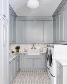 Gray u-shaped laundry room is clad in Cement Tile Shop Atlas Tiles lit by a vint. Gray u-shaped laundry room is clad in Cement Tile Shop Atlas Tiles lit by a vintage white glass sem Blue Laundry Rooms, Mudroom Laundry Room, Laundry Room Layouts, Laundry Room Cabinets, Blue Cabinets, Laundry Room Design, Mud Rooms, Laundry Room Floors, Small Laundry
