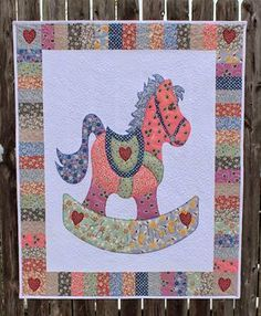 """Sweet appliqued rocking horse quilt made by Katie Wiseman from Katie's Quilts and Crafts for a friend's new baby. """"Here I am quilting a wide whimisical feather stitch with variegated polyester longarm thread by Aurifil."""" To see more please visit http://katiesquiltsandcrafts.blogspot.com/2014/04/rocking-horse-baby-quilt.html"""