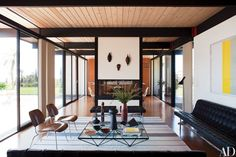 At a Malibu home restored and decorated by BoydDesign, prized vintage pieces balance the living room, including 1946 Eames rosewood chairs for Herman Mille and a midcentury Laverne leather-and-chrome sofa | archdigest.com