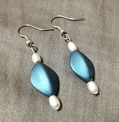 Small Soft Blue Triangle Earrings-(Soft Blue w/Pearl White Beads)-Womens.  Designed with a large soft blue triangle center bead, decorated with small pearl white beads on both ends.  Created by JadeADesigns and fits just about any outfit.  Please review shipping charges and details.