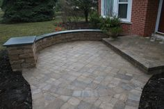 Stone patio with wall. Like how this is built up at the end. Would put a light on the raised end.