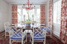 Faux bamboo chairs from CR Laine covered with Lulu DK fabric are mixed with red Schumacher draperies in the breakfast room. Light fixure is from Worlds Away.