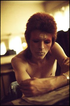 David in Ziggy makeup 1973. This shot was taken backstage on the British tour before a show. David was reading a review and I sneaked this shot with a zoom lens I already had on the Nikon so as not to disturb the Image. To this day I find it remarkable how calm he is only moments before showtime.      - Geoff MacCormack