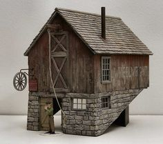 J.A. Whistler, Wheelwright. It is made from the usual stuff, cardboard and paper planking, a little strip wood, and this time lasercut cedar shingles from Full Steam Ahead. The stone part is cardboard (made thicker round window and door openings with balsa) covered in spackle compound and carved.