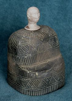 BMAC or Intercultural Style composite idol standing about 11.5 cm overall in height.  The body, with a squarish base is carved from chlorite and is decorated with incised geometric patterns. 3rd Millennium BC