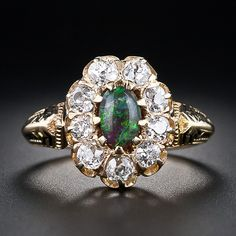 A fabulous black opal of modest size proudly shows its true and many peacock colors from within a halo of bright-white and beautiful old mine-cut diamonds, sparkling in buttercup settings, in this exquisite, rare and original antique Victorian ring accented with black enamel.