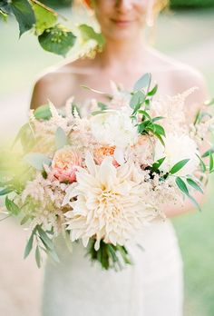 A loose bouquet comprised of dahlias, garden roses, astilbe, eucalyptus, and foraged greenery, arranged by Sofia of Branco Prata Studios.