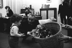 Lyndon B. Johnson presents a basket of puppies to the daughter of a White House staffer: