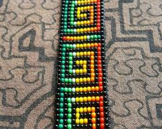These sacred bead work necklaces and bracelets are handmade by women from an indigenous cooperative from the Kamentsá tribe of the Sibundoy valley in southern Colombia. Each design is inspired by the visions received during traditional ceremonies. Bead Loom Bracelets, Beaded Bracelet Patterns, Bead Loom Patterns, Beading Patterns, Beadwork Designs, Loom Beading, Bead Weaving, Etsy, Paint
