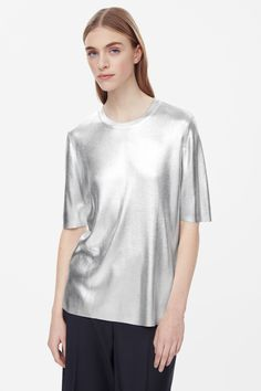 This rib knit top has a coated metallic finish with a light-catching effect. Designed for a close fit, it has a round neckline, short sleeves and minimal finishes. 115$