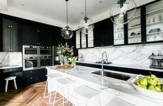 Black kitchen countertop marble kitchen island white splash bar stool parquet flooring