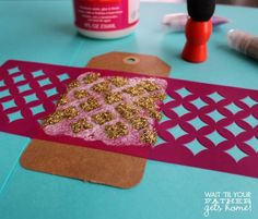 Make these beautiful stenciled glitter tags for your next gift using the new Mod Podge Rocks! Peel & Stick Stencils and podgeable glitters via www.waittilyourfathergetshome.com #modpodge #glitter #stencils