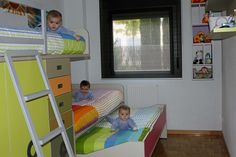 Dormitorio juvenil con una cama tren de tres camas, armario, cajones y estanterías.